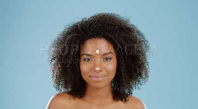 Buy stock photo Cropped shot of a young woman applying moisturizer to her face