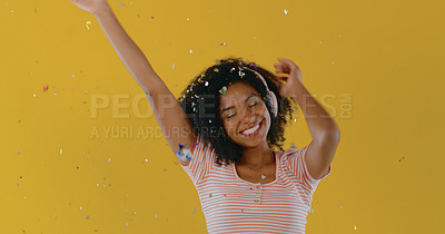 Buy stock photo Shot of a woman wearing headphone while having confetti fall over her