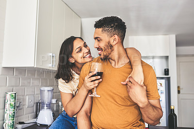 Buy stock photo Shot of a woman having a glass of wine while sitting in the kitchen with her boyfriend