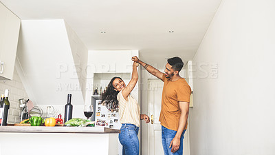 Buy stock photo Shot of an affectionate couple getting distracted by each other while cooking