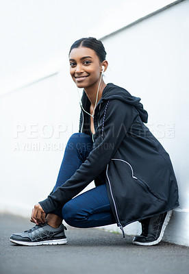 Buy stock photo Portrait of a sporty young woman tying her shoelaces while exercising outdoors