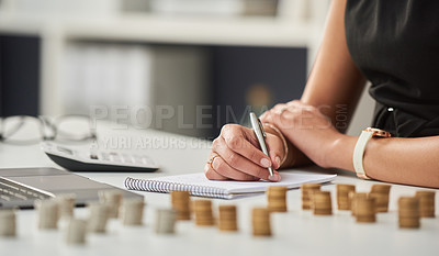 Buy stock photo Cropped shot of an unrecognizable businesswoman working out her finances with a calculator and a notepad in her office