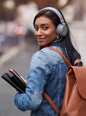 Buy stock photo Shot of a young woman walking through the city wearing headphones while carrying her books
