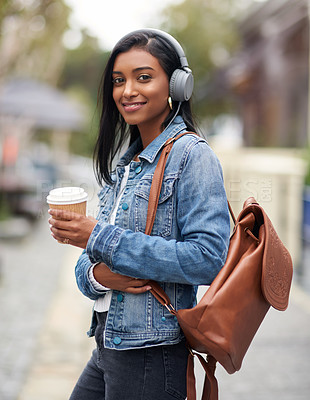 Buy stock photo Shot of a woman wearing headphones and holding a takeaway coffee outdoors