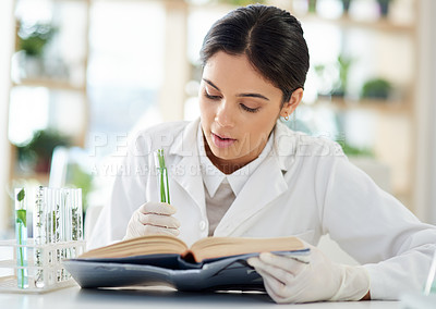 Buy stock photo Shot of a young scientist reading a book while working with plant samples in a lab