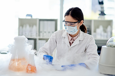 Buy stock photo Shot of a young scientist doing an experiment in a lab
