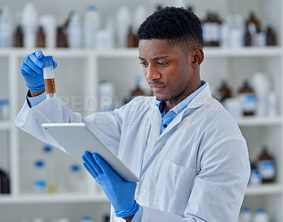 Buy stock photo Cropped shot of a focused young male scientist working on a digital tablet while studying a vial with a substance inside of it at a laboratory