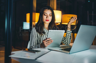 Buy stock photo Shot of a young businesswoman using a digital tablet and laptop during a late night at work
