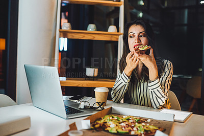 Buy stock photo Shot of a young businesswoman having pizza and using a laptop during a late night at work