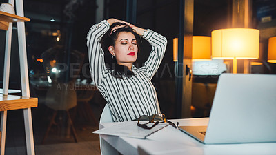 Buy stock photo Shot of a young businesswoman taking a break while working at her desk late at night
