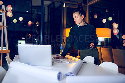 Buy stock photo Cropped shot of an attractive young female architect looking thoughtful while working late in a modern office