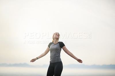 Buy stock photo Shot of a sporty young woman standing with her arms outstretched outdoors