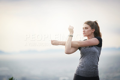 Buy stock photo Shot of a sporty young woman stretching her arms while exercising outdoors