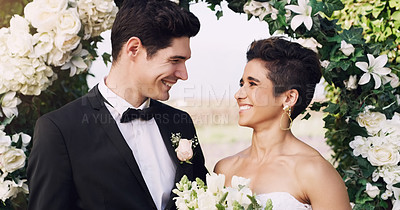 Buy stock photo Cropped shot of an affectionate young newlywed couple smiling at each other while standing outdoors on their wedding day