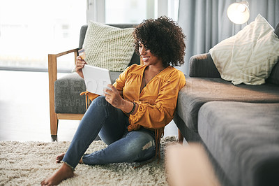 Buy stock photo Cropped shot of an attractive young woman sitting on her living room floor and using her tablet for online shopping