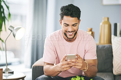 Buy stock photo Shot of a young man using a smartphone while relaxing on the sofa at home