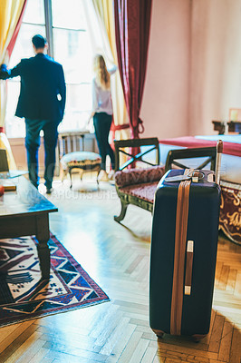 Buy stock photo Shot of a suitcase inside a hotel room with two businesspeople standing in the background