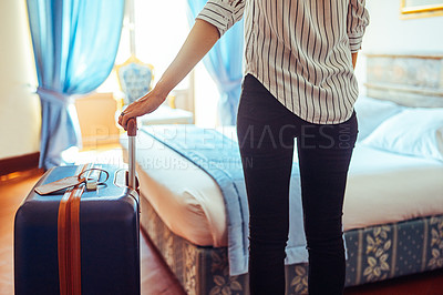 Buy stock photo Cropped shot of an unrecognizable businesswoman standing with her suitcase inside a hotel room