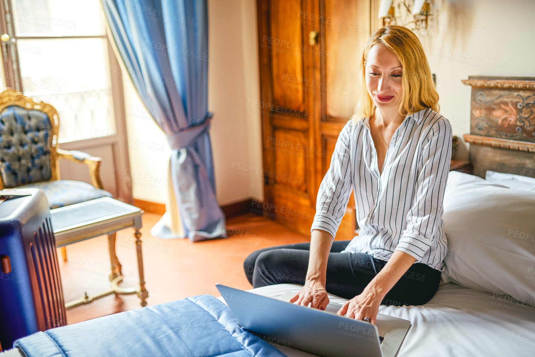 Buy stock photo Shot of an attractive young businesswoman sitting on a bed and using a laptop inside her hotel room