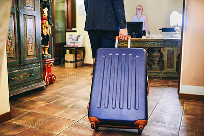 Buy stock photo Cropped shot of an unrecognizable businessman walking with his suitcase to check in at the hotel reception