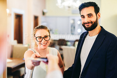 Buy stock photo Shot of a happy young couple handing over their tickets and checking in at a hotel