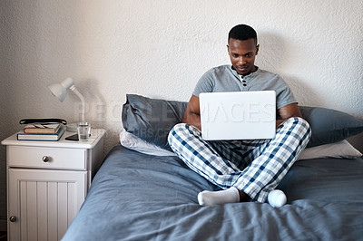 Buy stock photo Full length shot of a handsome young man sitting alone on his bed and using his laptop at home