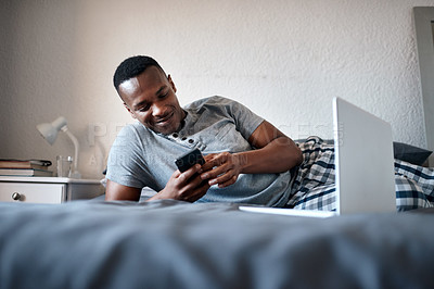Buy stock photo Cropped shot of a handsome young man lying down on his bed and using his cellphone while at home alone