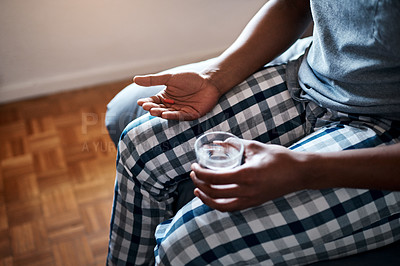 Buy stock photo Cropped shot of an unrecognizable man sitting alone on his bed and taking painkillers with water