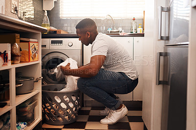 Buy stock photo Shot of a man doing the laundry at home