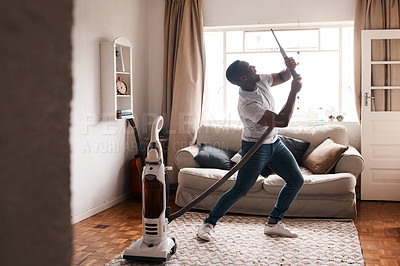 Buy stock photo Shot of a young man dancing while busy vacuuming the living room