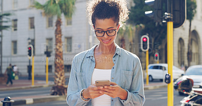 Buy stock photo Cropped shot of an attractive young woman standing alone and texting on her cellphone while sightseeing in the city
