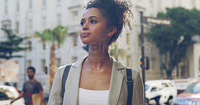 Buy stock photo Cropped shot of an attractive young woman standing and looking contemplative while sightseeing in the city alone