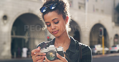 Buy stock photo Cropped shot of an attractive young woman standing in the city and looking at the pictures taken on her camera