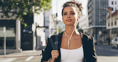 Buy stock photo Cropped shot of an attractive young woman walking through the city and listening to music through her earphones