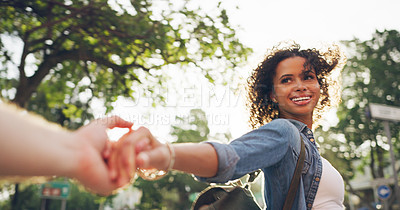 Buy stock photo Cropped shot of an attractive young woman holding hands with her boyfriend and leading him through the city