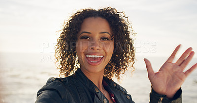 Buy stock photo Cropped shot of an attractive young woman standing with the ocean behind her and waving at the camera