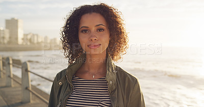 Buy stock photo Cropped shot of an attractive young woman standing alone with the ocean behind her while sightseeing the city