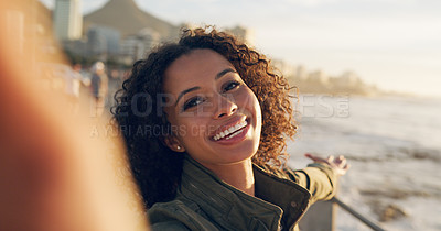 Buy stock photo Cropped shot of an attractive young woman standing alone and taking a selfie with the ocean behind her