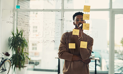 Buy stock photo Shot of a young businessman looking thoughtful while brainstorming with notes on a glass wall in an office