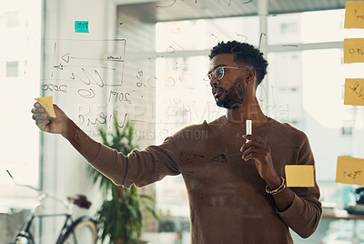 Buy stock photo Shot of a young businessman brainstorming with notes on a glass wall in an office