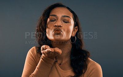 Buy stock photo Studio shot of an attractive young woman blowing a kiss with her eyes closed while standing against a grey background