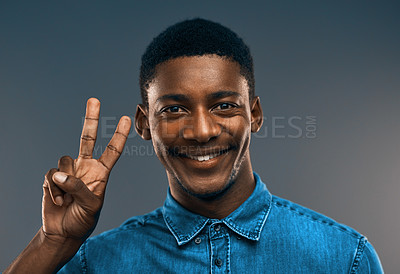 Buy stock photo Studio portrait of a handsome young man making the peace sign against a grey background