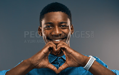 Buy stock photo Studio portrait of a handsome young man smiling while making a heart shape against a grey background