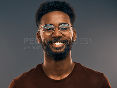 Buy stock photo Studio portrait of a handsome young man smiling while standing against a grey background