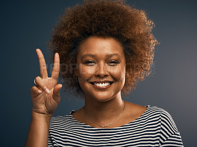 Buy stock photo Studio portrait of an attractive young woman showing the peace sign while standing against a grey background