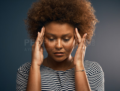 Buy stock photo Studio shot of an attractive young woman suffering with a headache while standing against a grey background