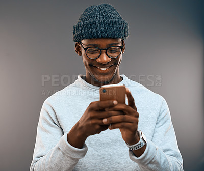 Buy stock photo Studio shot of a handsome young man using a smartphone while standing against a grey background
