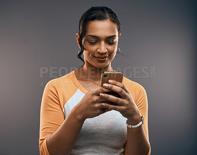 Buy stock photo Studio shot of an attractive young woman using a smartphone while standing against a grey background