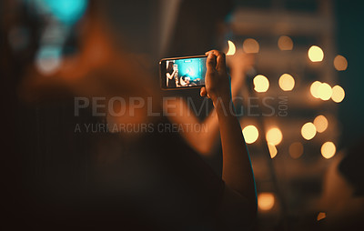 Buy stock photo Closeup shot of an unrecognisable woman in the audience capturing a performance at the club on a cellphone