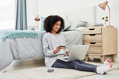 Buy stock photo Full length shot of an attractive young woman sitting on her bedroom floor and using her laptop for online shopping